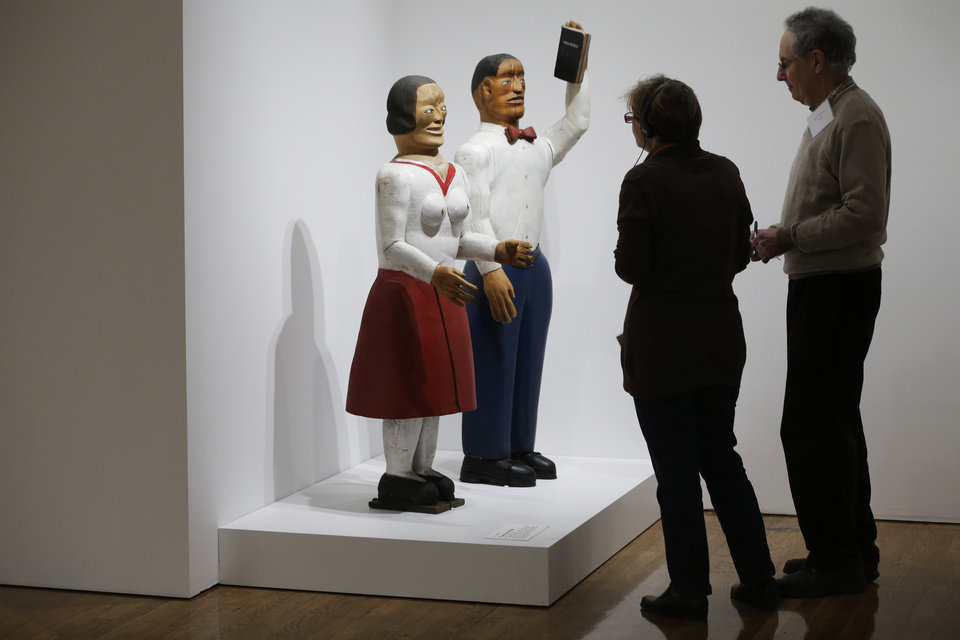 """Photo - People view a S. L. Jones sculpture titled Preacher and His Wife, during a press preview for """"Great and Mighty Things"""": Outsider Art from the Jill and Sheldon Bonovitz Collectionat the Philadelphia Museum of Art Friday, March 1, 2013, in Philadelphia. The exhibition is scheduled to run from March 3, 2013 - June 9, 2013. (AP Photo/Matt Rourke)"""