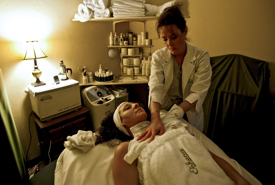 Photo - Denice Elwell of Enhance Skin Care and Massage applies a chocolate facial to Michelle Marcuzzo at the salon on Monday, Feb. 9, 2009, in Oklahoma City, Okla. Elwell will be providing the treatments at Mustang's upcoming Chocolate Festival.  PHOTO BY CHRIS LANDSBERGER, THE OKLAHOMAN