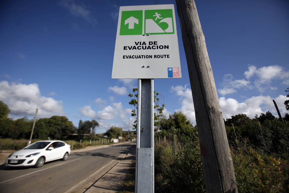 In this Nov. 29, 2012 photo, a car drives by a sign indicating the evacuation route in the event of a tsunami, in Navidad, Chile. The road to the town of Navidad (Christmas in Spanish) is lined by a forest of eucalyptus trees and wildflowers that grow around painted tsunami warning signs that urge residents to build their homes high or dash for higher ground in case of a quake. (AP Photo/Luis Hidalgo)