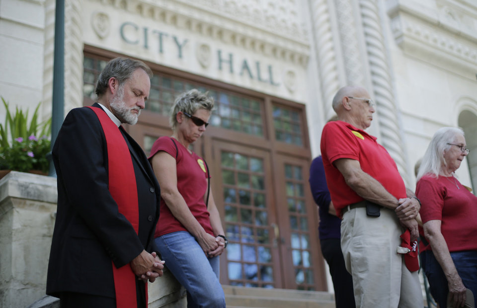 Photo - Pastor Paul Ziese, left, prays with other Faith leaders who support a proposed non-discrimination ordinance on the steps of City Hall, Tuesday,  Sept. 3, 2013, in San Antonio. The San Antonio city council will vote Thursday on the ordinance which in part would prohibit discrimination based on sexual orientation and gender identity. (AP Photo/Eric Gay)