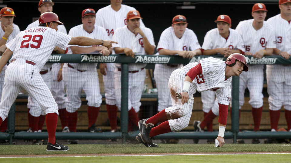 Photo - Oklahoma's Hunter Lockwood gets up to run back to third after falling down as coach Sunny Golloway gives instructions during the fourth inning of their baseball game against Arkansas at L. Dale Mitchell Park in Norman, Okla., Tuesday, April 10, 2012. Photo by Bryan Terry, The Oklahoman