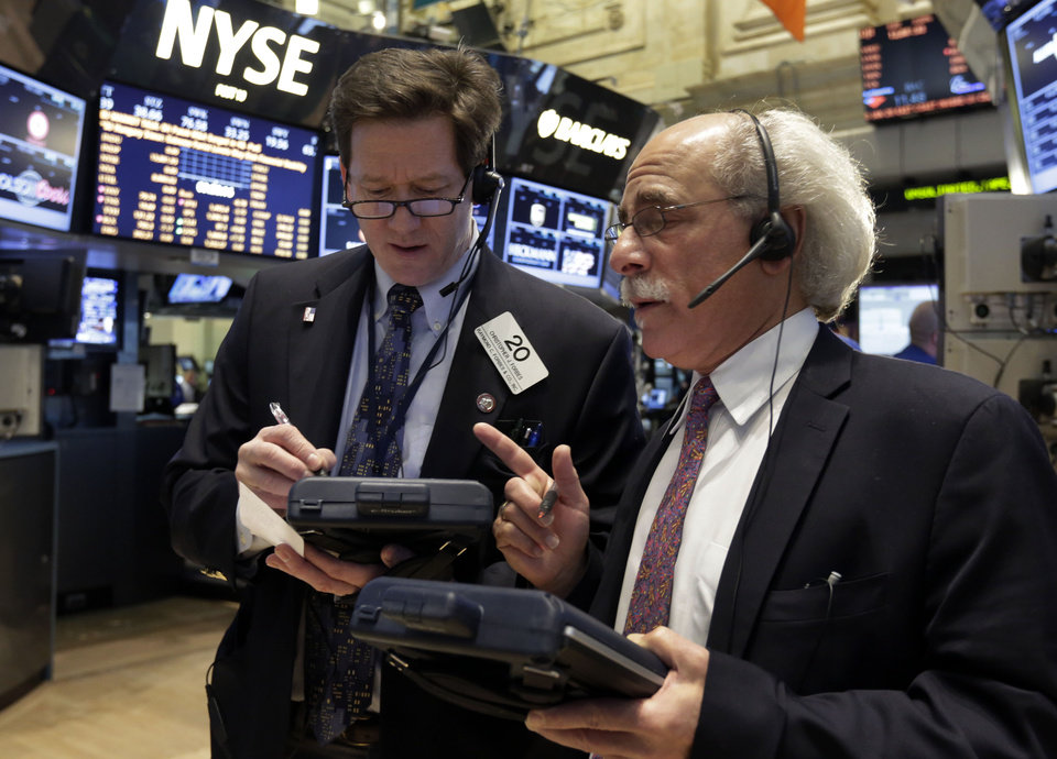 Traders Christopher Forbes, left, and Peter Tuchman work on the floor of the New York Stock Exchange,Tuesday, Jan. 29, 2013. Stocks opened mixed on Wall Street, with the Standard & Poor's 500 holding at 1,500. (AP Photo/Richard Drew)