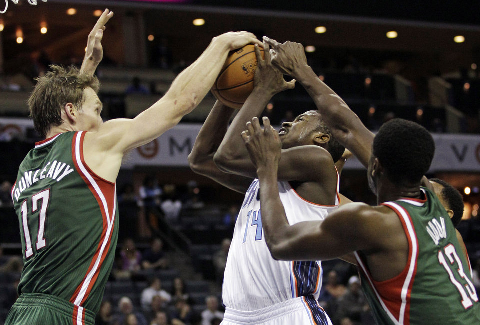 Charlotte Bobcats' Michael Kidd-Gilchrist (14) has his shot blocked by Milwaukee Bucks' Mike Dunleavy (17) and Ekpe Udoh (13) during the first half of an NBA basketball game in Charlotte, N.C., Monday, Nov. 19, 2012. (AP Photo/Chuck Burton)