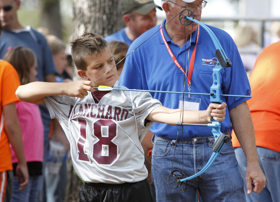 Photo - Steve Loveland watches as ten year old Caden Frazier uses a bow and arrow during school day of the Oklahoma Wildlife Expo at the Lazy E Arena and Ranch in Guthrie, OK, Friday, September 28, 2012,  By Paul Hellstern, The Oklahoman