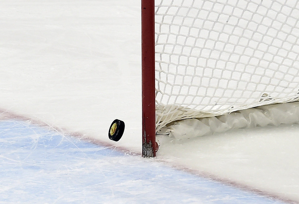 Photo - The puck hits the post with Canada's goalie pulled in the last minutes of the third period of the gold-medal women's hockey game between Canada and the United States at the Sochi Winter Olympics in Sochi, Russia, on Thursday, Feb. 20, 2014. Canada scored in the final minute of regulation, and won 3-2 in overtime. (AP Photo/The Canadian Press, Nathan Denette)