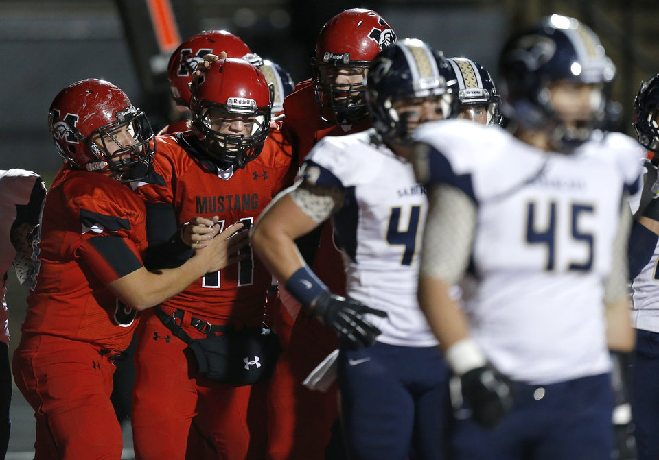 Mustang's Chandler Garrett, center, celebrates with Jaxon Taylor after a touchdown against Southmoore during their high school football game in Mustang, Okla., Friday, November 8, 2013. Photo by Bryan Terry, The Oklahoman