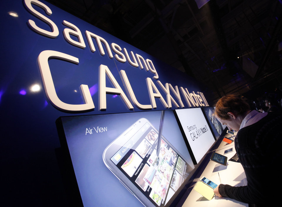 Photo -   Attendees try out the new Samsung Galaxy Note II during a launch event, Wednesday, Oct. 24, 2012, in New York. Aside from the 5.5 inch screen, the Note comes with a stylus and runs the latest version of Google's Android operating system, Jelly Bean. (AP Photo/Jason DeCrow)