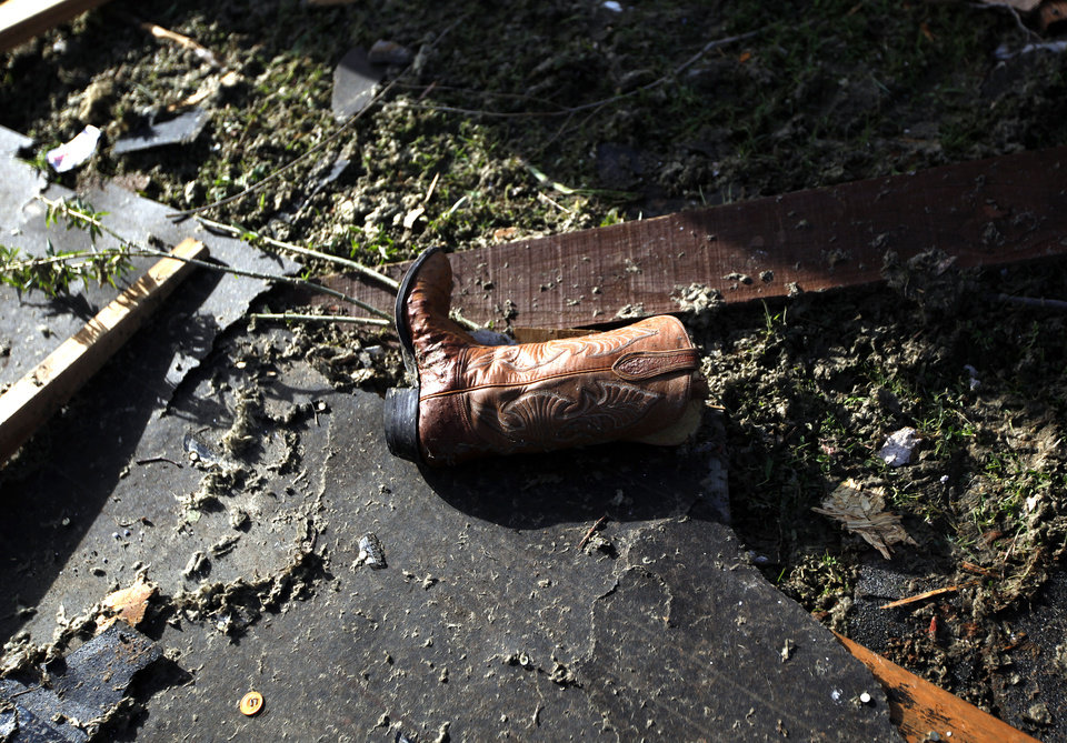 Photo - A cowboy boots sits in a yard, Sunday, April 15, 2012.  A tornado struck Woodward early Sunday morning. Photo by Sarah Phipps, The Oklahoman.