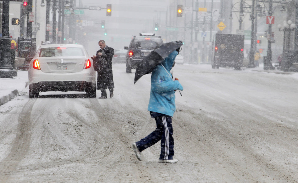 A man uses an umbrella to ward off snow as he crosses a street in Denver\'s financial district on Tuesday, April 9, 2013. A blizzard forecast for the area did not materialize. Instead as much as four inches of snow could fall on the Mile High City. (AP Photo/Ed Andrieski)
