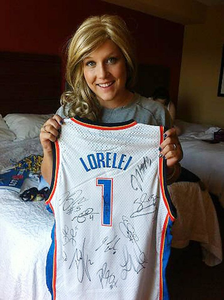 Photo - THUNDER CARES / NBA BASKETBALL TEAM: Lorelei Decker shows off her signed Oklahoma City Thunder jersey.