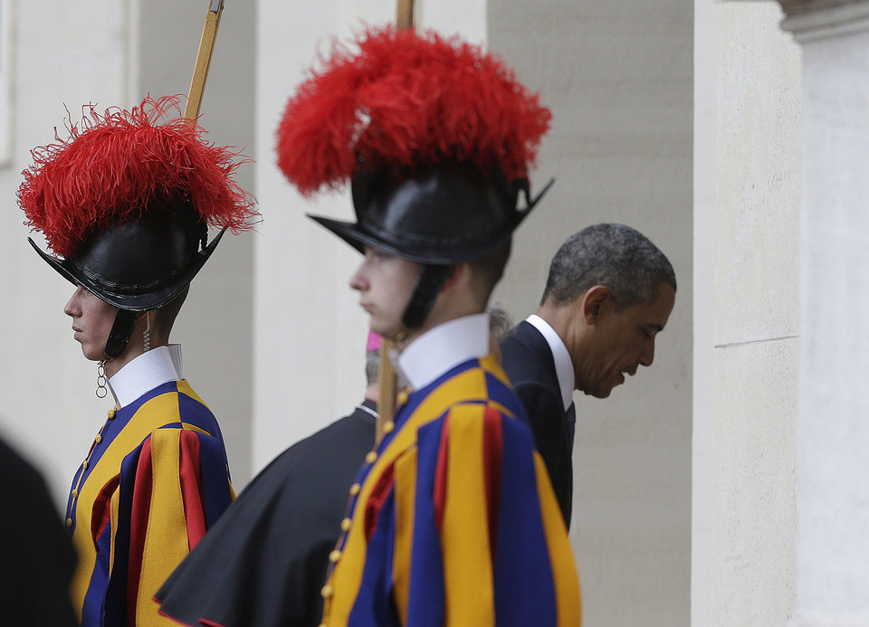 Photo - President Barack Obama walks past two Vatican Swiss guards as he arrives at the Vatican to meet Pope Francis, Thursday, March 27, 2014. Obama is the ninth president to make an official visit to the Vatican. His audience marks a change of pace for the president, who has devoted the past three days of a weeklong, four-country trip to securing European unity against Russia's aggressive posture toward Ukraine. (AP Photo/Alessandra Tarantino)