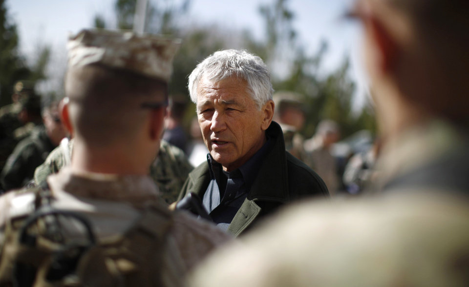 Photo - U.S. Secretary of Defense Chuck Hagel, center, talks with members of the U.S. Army and Marines during his visit to the Kabul Military Training Center in Kabul, Afghanistan, Sunday, March 10, 2013. Hagel is on his first trip to Afghanistan as defense secretary. (AP Photo/Jason Reed, Pool)