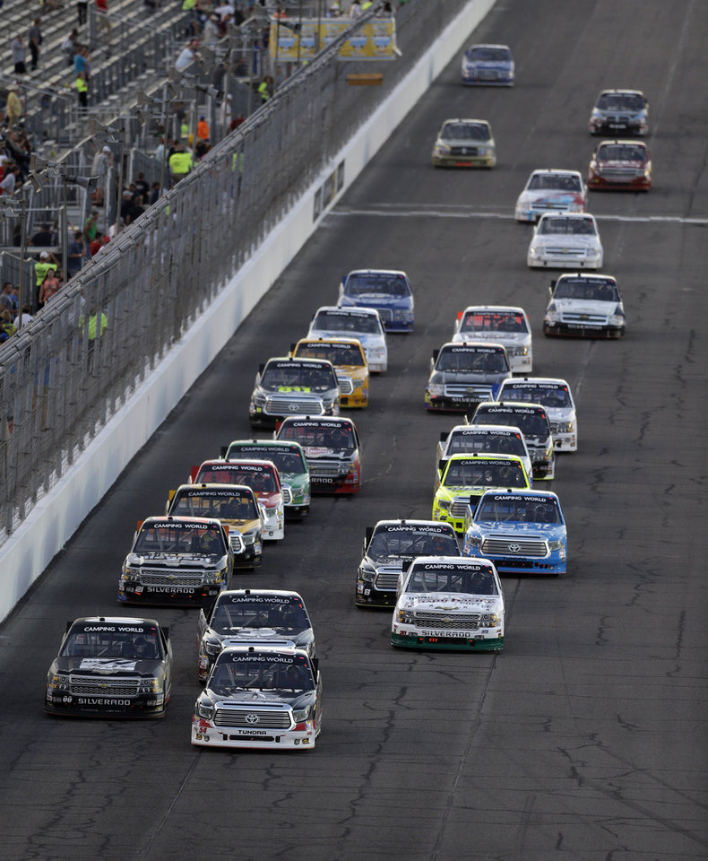 Photo - Drivers vie for position during the NASCAR Truck Series auto race at Gateway Motorsports Park on Saturday, June 14, 2014, in Madison, Ill. (AP Photo/Jeff Roberson)