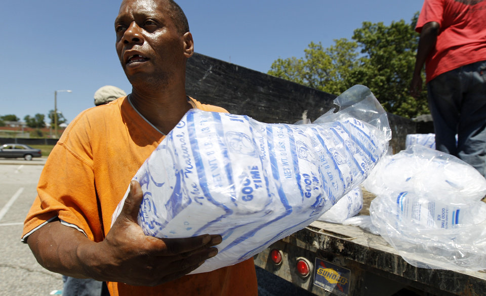 Photo -   Baltimore city worker Joe Lane give away free bags of ice to residents at the Northwood Plaza shopping center, in Baltimore on Monday, July 2, 2012. Around 2 million customers from North Carolina to New Jersey and as far west as Illinois were without power Monday morning after a round of summer storms. (AP Photo/Jose Luis Magana)