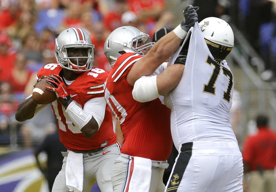 Photo - Ohio State quarterback J.T. Barrett, left, looks for a receiver as center Jacoby Boren blocks Navy guard Bernard Sarra during the first half of an NCAA college football game in Baltimore, Saturday, Aug. 30, 2014. (AP Photo/Patrick Semansky)