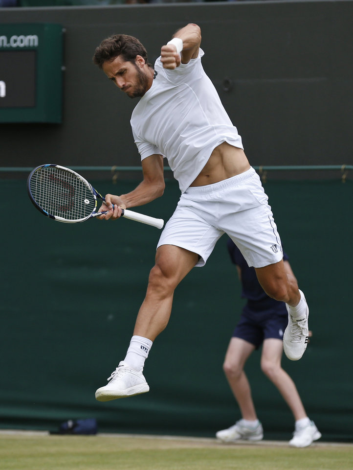 Photo - Feliciano Lopez of Spain celebrates winning a game to John Isner of the U.S. in their men's singles match at the All England Lawn Tennis Championships in Wimbledon, London, Monday, June 30, 2014. (AP Photo/Sang Tan)