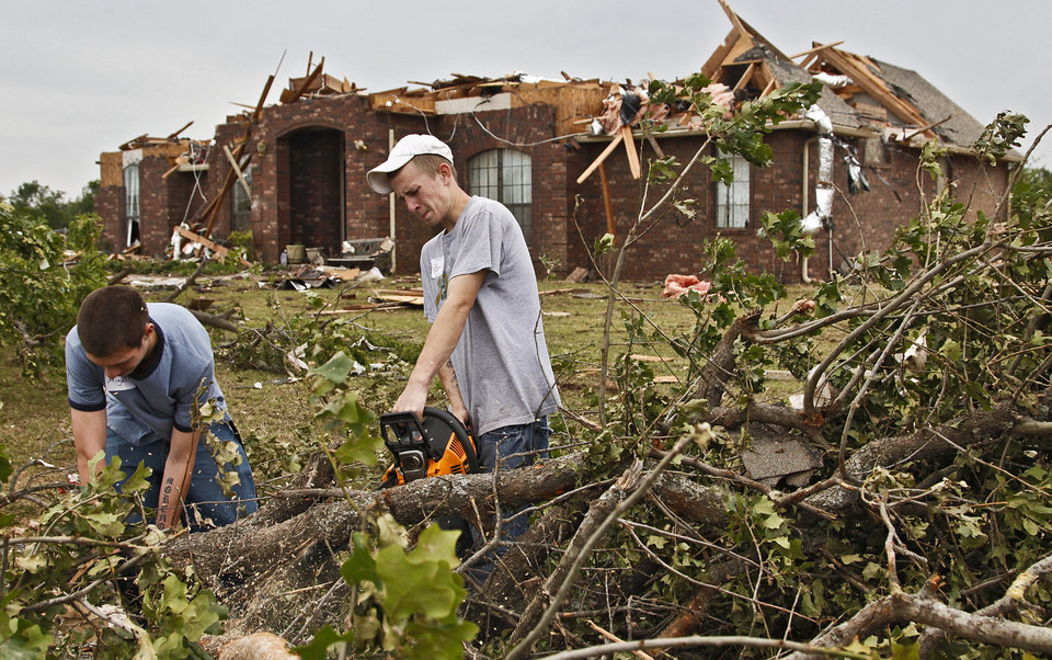 Photo - STORM DAMAGE / CLEANUP / AFTERMATH / VOLUNTEERS: Little Axe students Miguel Varnell and Ben Dodson, from left, help clean up debris and damage on Wednesday, May 12, 2010, in Oklahoma City, Okla. left behind by the tornados that hit central oklahoma on Monday. Varnell and Dodson volunteered their time to help clean up a neighborhood near 59th and Peebly Road after their school was destroyed by a tornado.  Photo by Chris Landsberger, The Oklahoman  ORG XMIT: KOD
