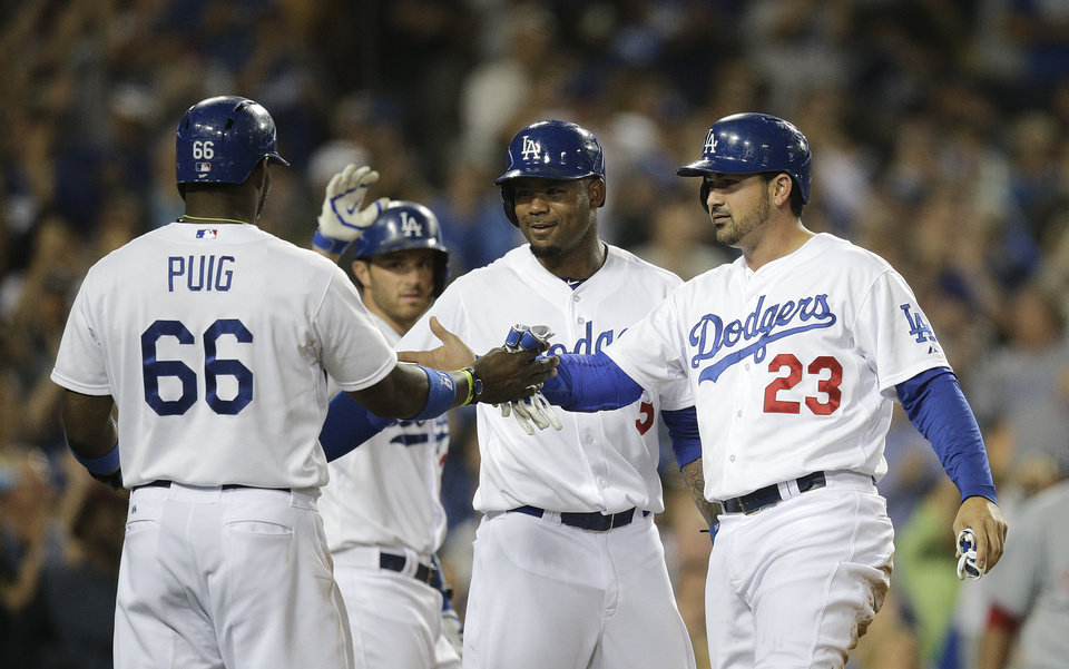 Photo - Los Angeles Dodgers' Yasiel Puig, Carl Crawford and Adrian Gonzalez, from left, celebrate after they scored on a triple hit Andre Ethier during the fourth inning of a baseball game against the Cincinnati Reds on Tuesday, May 27, 2014, in Los Angeles. (AP Photo/Jae C. Hong)