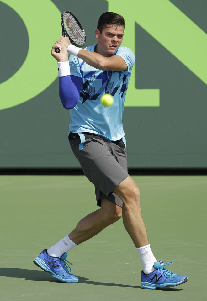 Photo - Milos Raonic, of Canada, returns the ball to Guillermo Garcia-Lopez, of Spain, during the Sony Open tennis tournament, Monday, March 24, 2014, in Key Biscayne, Fla. (AP Photo/Luis M. Alvarez)