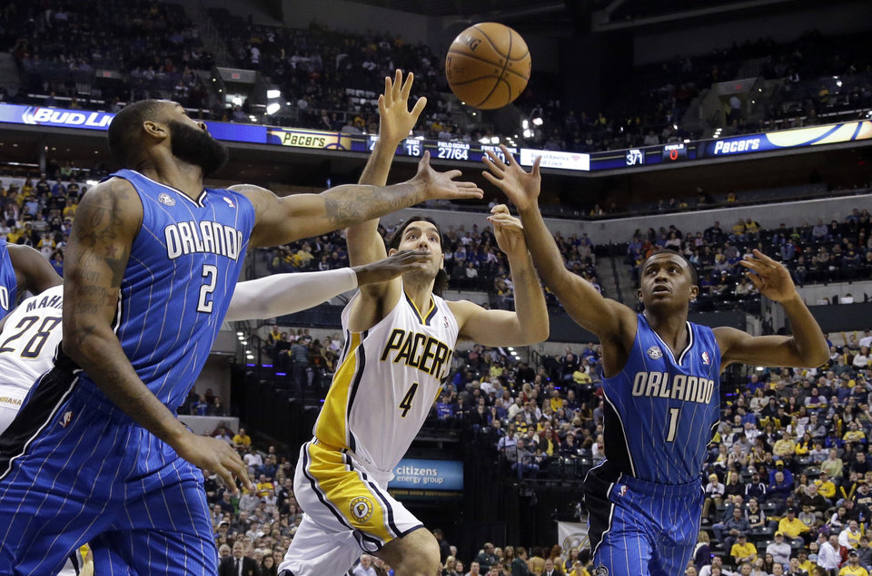 Photo - Indiana Pacers forward Luis Scola, center, along with Orlando Magic forward Kyle O'Quinn, left, and shooting guard Doron Lamb go for a loose all in the second half of an NBA basketball game in Indianapolis, Monday, Feb. 3, 2014. The Pacers defeated the Magic 98-79. (AP Photo/Michael Conroy)
