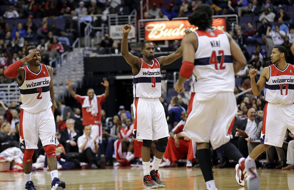 Photo - Washington Wizards guard John Wall (2), forward Martell Webster (9) and guard Garrett Temple (17) celebrate a 3-point shot in the second half of an NBA basketball game against the Los Angeles Clippers Monday, Feb. 4, 2013 in Washington. The Wizards won 98-90. (AP Photo/Alex Brandon)