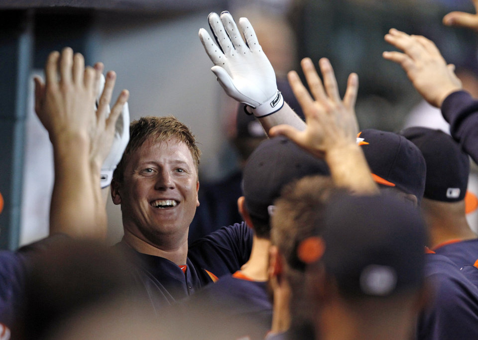 Photo - Houston Astros's Marc Krauss celebrates with teammates in the dugout after hitting a solo home run in the second inning of a baseball game against the Los Angeles Angels Sunday, Sept. 15, 2013, at Minute Maid Park in Houston. (AP Photo/Eric Christian Smith)