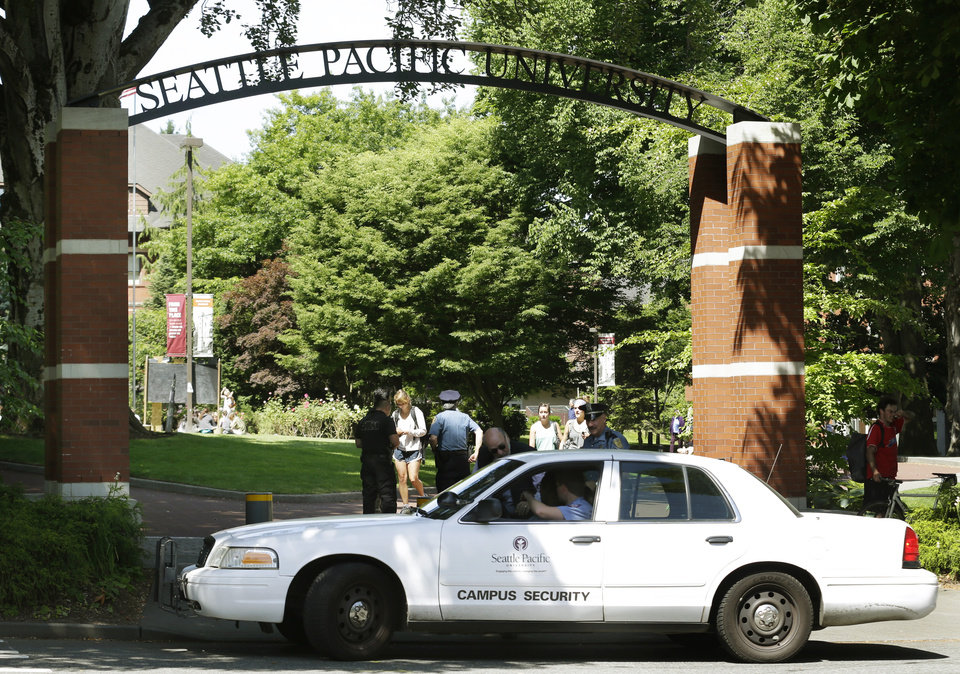 Photo - A campus security vehicle stops briefly in front of an arched entrance at Seattle Pacific University in Seattle, Friday, June 6, 2014, the day after a fatal shooting at the university. (AP Photo/Ted S. Warren)
