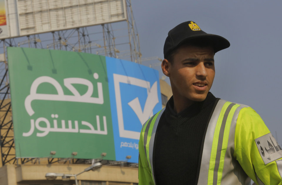 Photo - An Egyptian traffic policeman stands under a billboard with Arabic that reads,