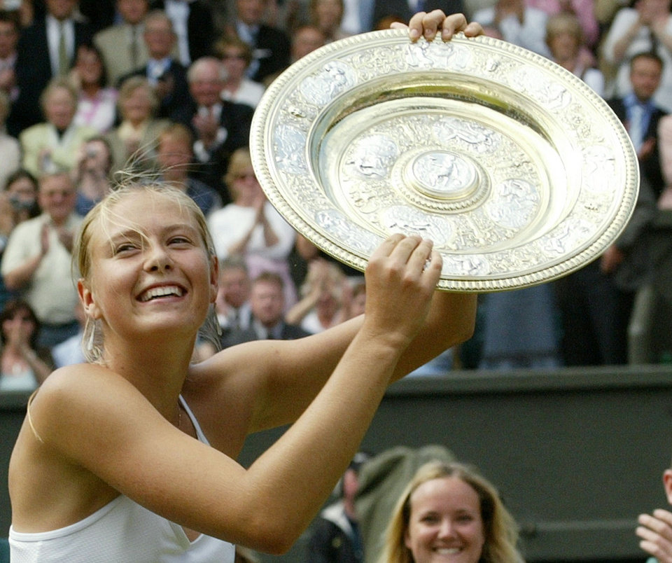 Photo - ADVANCE FOR WEEKEND EDITIONS, JUNE 21-22 - FILE - In this July 3, 2004, file photo, Russia's Maria Sharapova holds the winner's trophy after defeating Serena Williams in the  women's Singles final tennis match on the Centre Court at Wimbledon. Sharapova won Wimbledon at age 17 for her first Grand Slam title. Now she's got five major trophies, but is still stuck on one at the All England Club.   (AP Photo/Anja Niedringhaus, File)