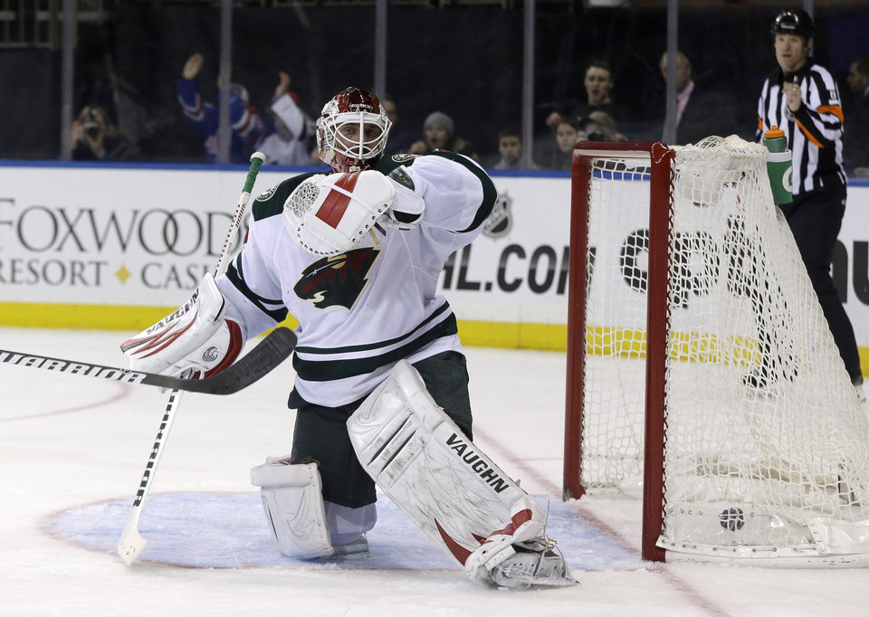 Photo - Minnesota Wild goalie Niklas Backstrom reacts after being scored on by New York Rangers' Carl Hagelin during the second period of an NHL hockey game, Sunday, Dec. 22, 2013, in New York. (AP Photo/Seth Wenig)