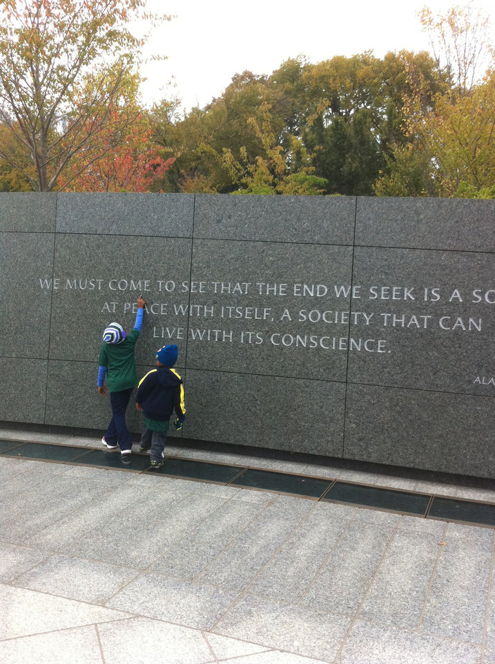 Photo - A young child traces the words from one of 14 quotations from Martin Luther King Jr. that are on the wall which surround the monument. PHOTO BY JOE HIGHT, THE OKLAHOMAN
