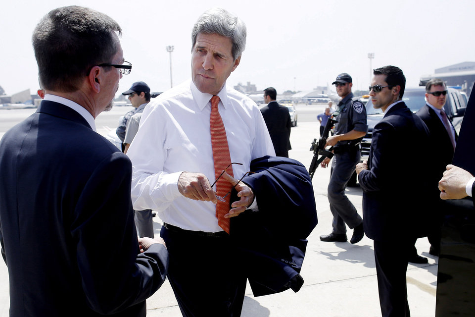 Photo - U.S. Secretary of State John Kerry, center, talks with U.S. Embassy Deputy Chief of Mission Bill Grant after his arrival in Tel Aviv, Israel, Wednesday, July 23, 2014. Kerry is meeting with U.N. Secretary-General Ban Ki-moon, Israeli Prime Minister Benjamin Netanyahu, and Palestinian Authority President Mahmoud Abbas as efforts for a cease-fire between Hamas and Israel continues. (AP Photo/Pool)