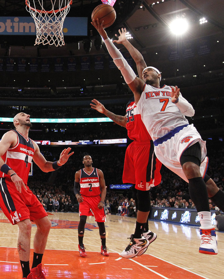 Photo - FILe - In this Dec. 16, 2013 file photo, New York Knicks' Carmelo Anthony (7) goes to the basket against Washington Wizards' Trevor Booker (35) during the first half of an NBA basketball game in New York. Signing day has arrived in the NBA, if the biggest free agents care to grab their pens. But it's unclear if Carmelo Anthony, Chris Bosh and Dwyane Wade _ who all might be waiting on LeBron James to go first _ are ready.(AP Photo/Jason DeCrow, File)