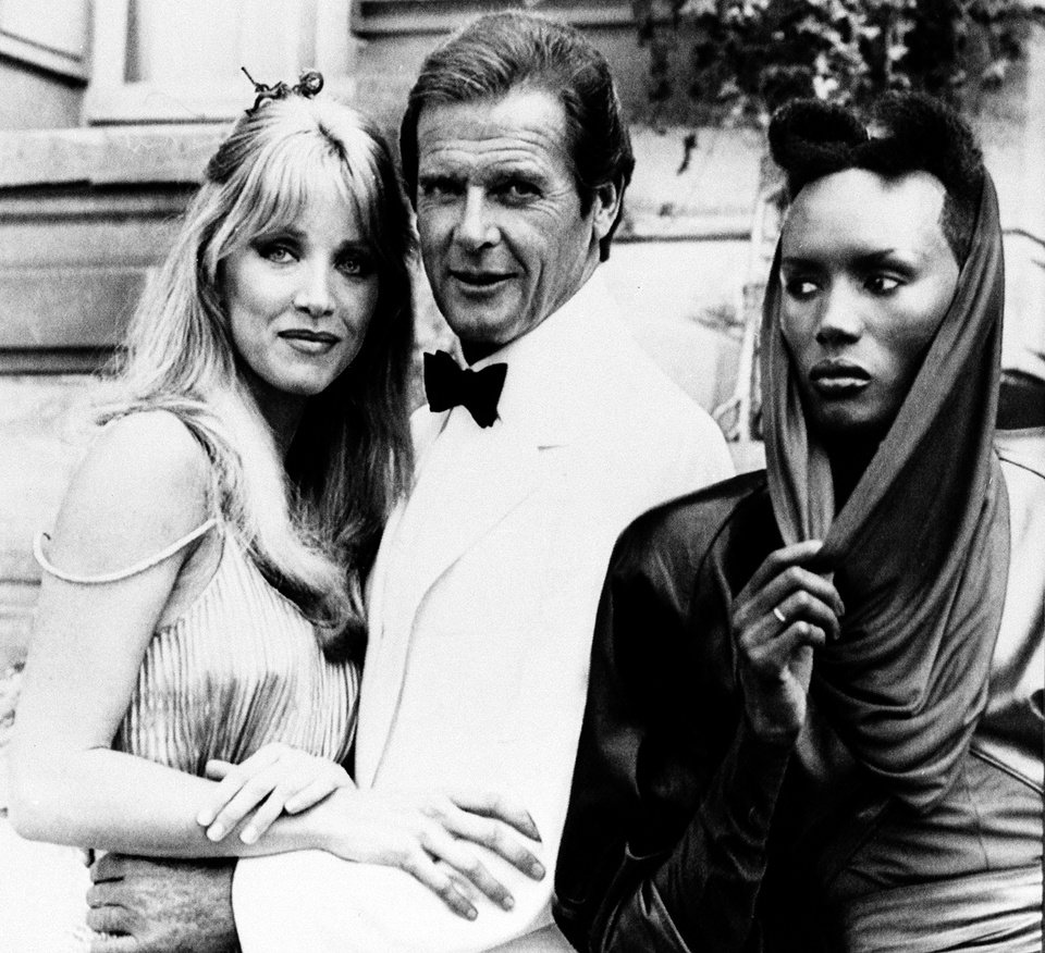 """FILE - In this Aug. 17, 1984 file photo, actor Roger Moore, alias British secret agent James Bond, is seen with his co-stars Tanya Roberts, and Grace Jones, right, in front of Chateau de Chantilly, on the set of the 007 action film """"A View to a Kill,"""" near Paris, France. (AP Photo/Alexis Duclos, File)"""