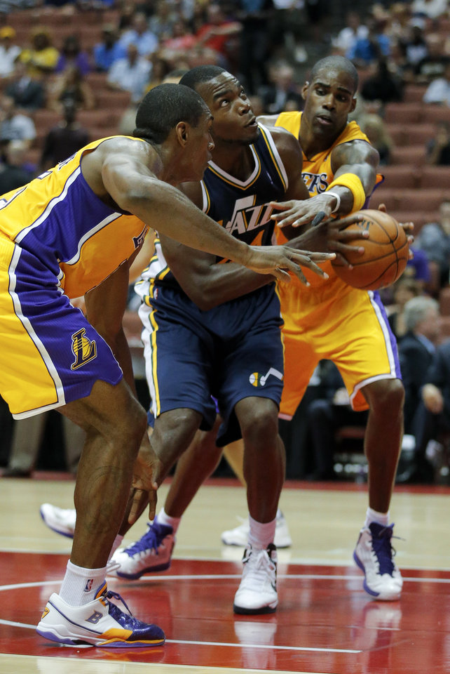 Photo -   Utah Jazz's Paul Millsap, center, looks to shoot as he is defended by Los Angeles Lakers' Metta World Peace, left, and Antawn Jamison during the first half of an NBA preseason basketball game in Anaheim, Calif., Tuesday, Oct. 16, 2012. (AP Photo/Jae Hong)