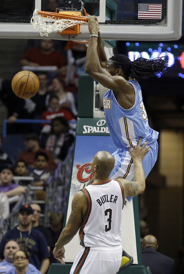 Photo - Denver Nuggets' Kenneth Faried dunks over Milwaukee Bucks' Caron Butler during the second half of an NBA basketball game Thursday, Feb. 20, 2014, in Milwaukee. (AP Photo/Jeffrey Phelps)