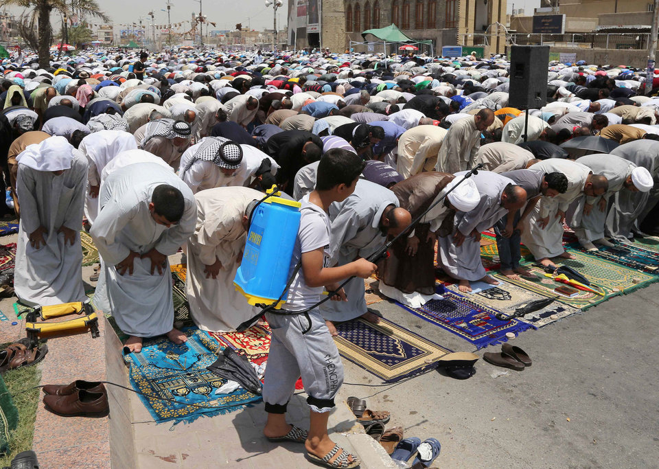 Photo - A boy sprays water over followers of Shiite cleric Muqtada al-Sadr as they practice open-air Friday prayers in the Shiite stronghold of Sadr City, Baghdad, Iraq, Friday, July 4, 2014. (AP Photo/Karim Kadim)