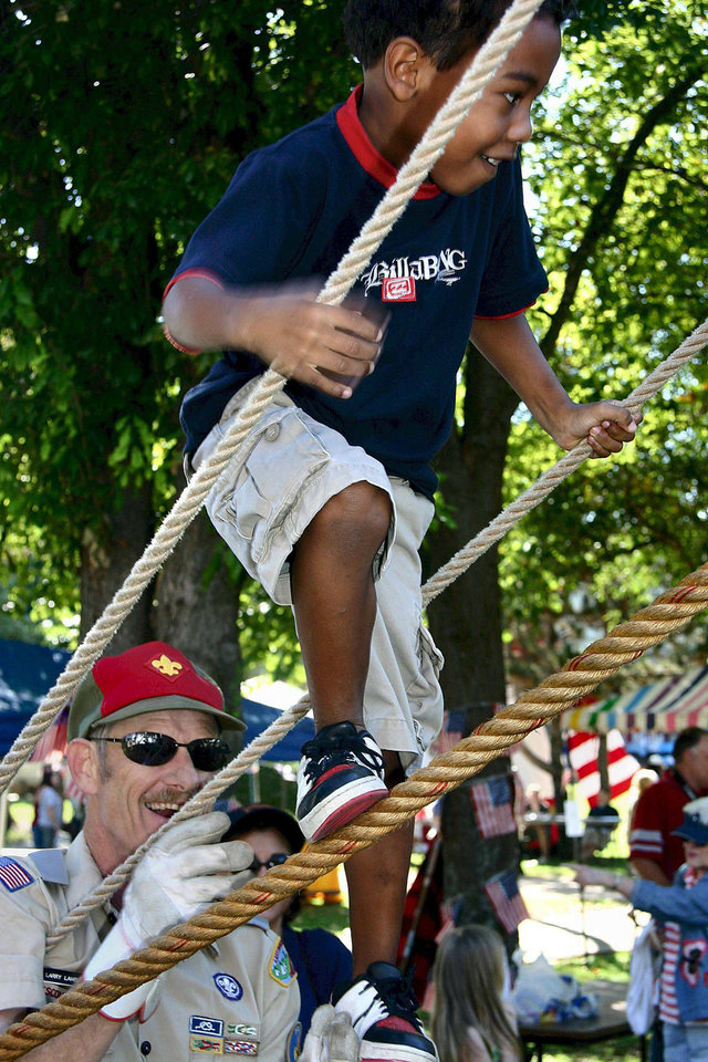 Larry Lambertus, of Big Tepee District of the Boy Scouts of America, assists an unidentified young boy to climb the rope monkey bridge at Rose State College's Global Oklahoma Festival of Cultures.  Imaged on October 7, 2006.<br/><b>Community Photo By:</b> mark d. doiron<br/><b>Submitted By:</b> Mark, Midwest City