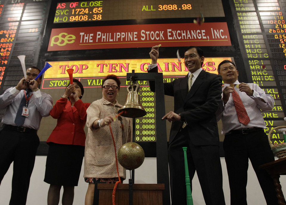 Photo - Philippine Stock Exchange President and CEO Hans Sicat, second from right, gestures as PSE treasurer Ma. Vivian Yuchengco rings the bell to signal the start of the first day of trading at Philippine Stock Exchange at the financial district of Makati, south of Manila, Philippines on Wednesday Jan. 2, 2013. Stock markets in Asia registered relief Wednesday over the U.S. congressional vote to stop hundreds of billions of dollars in automatic tax increases and spending cuts that risked plunging the world's biggest economy into recession. (AP Photo/Aaron Favila)