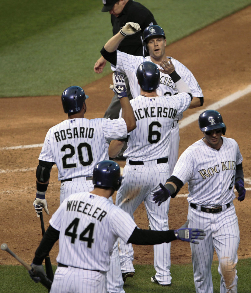 Photo - Colorado Rockies' Wilin Rosario (20) and Corey Dickerson (6) congratulate Justin Morneau, top, after his three-run home run in the fourth inning against the St. Louis Cardinals in a baseball game in Denver on Tuesday, June 24, 2014. Rockies' Ryan Wheeler (44) greets Troy Tulowitzki (2). (AP Photo/Joe Mahoney)