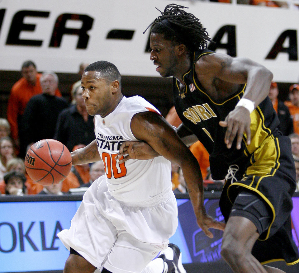 Photo - OSU's Byron Eaton dribbles past Missouri's DeMarre during the Big 12 college basketball game between Oklahoma State and Missouri at Gallagher-Iba Arena in Stillwater, Okla., Wednesday, Jan. 21, 2009.  PHOTO BY BRYAN TERRY, THE OKLAHOMAN