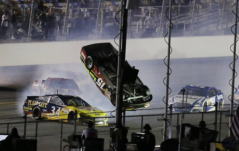 Photo - Clint Bowyer (15) flips upside down as he is involved in a multi-car crash with David Ragan (34), Carl Edwards (99) and others on the final lap of  the second of two NASCAR Sprint Cup qualifying auto races at Daytona International Speedway in Daytona Beach, Fla., Thursday, Feb. 20, 2014. (AP Photo/John Raoux)