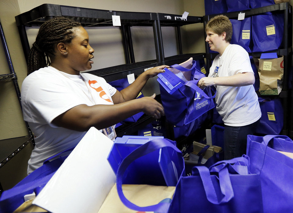 Photo - Volunteer Christy Davison and Chief Programs Officer Robyn Hilger load a cart with school supplies for teachers Wednesday at the Foundation for Oklahoma City Public Schools. Photo by Nate Billings, The Oklahoman