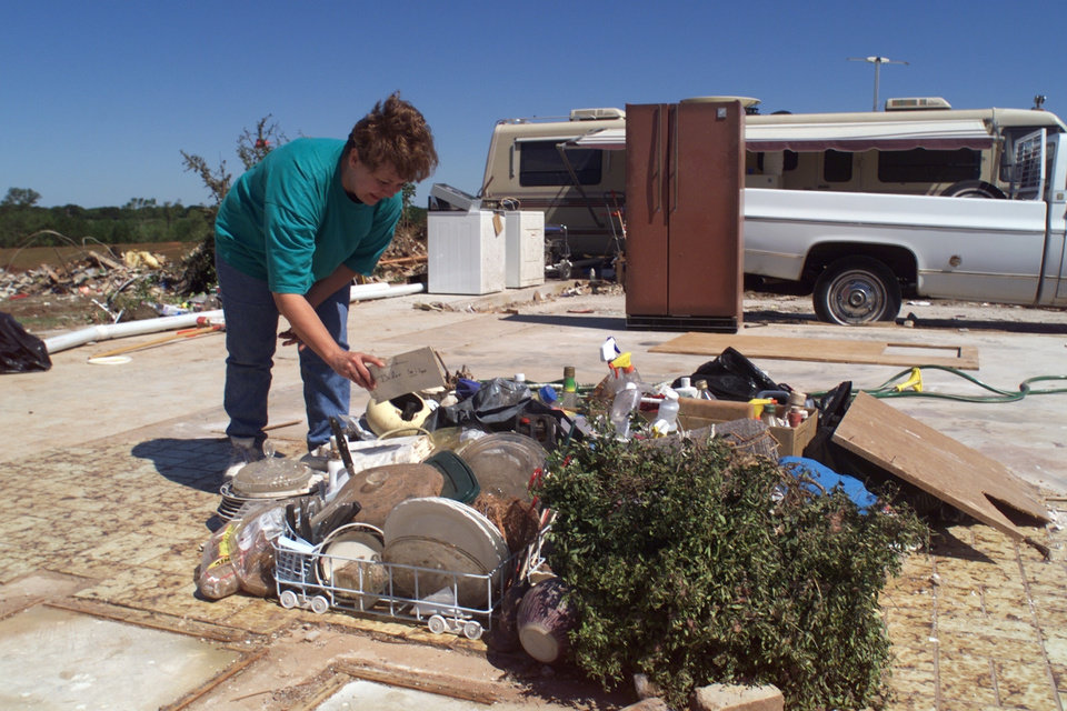 Tornado damage, victim: Margaret Mobley looks through some salvaged belongings stacked on the concrete slab of her missing house. In the background is her motor home which volunteers have hooked up to utilities, and some appliances which have been donated.