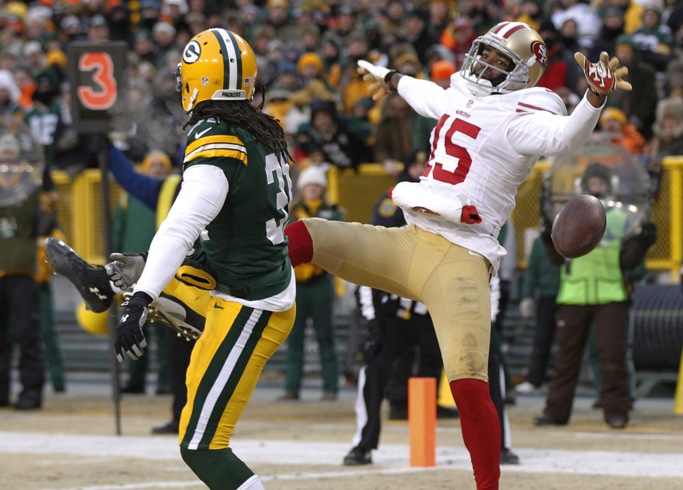 Photo - Green Bay Packers cornerback Davon House (31) breaks up a pass intended for San Francisco 49ers wide receiver Michael Crabtree (15) during the first half of an NFL wild-card playoff football game, Sunday, Jan. 5, 2014, in Green Bay, Wis. (AP Photo/Mike Roemer)