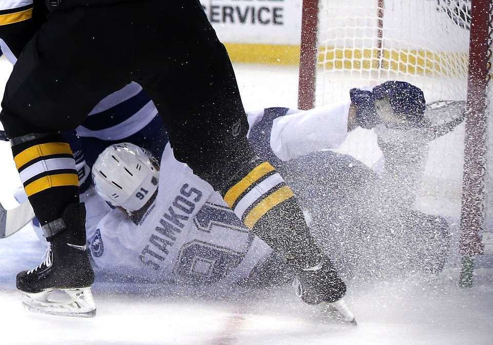 Photo - Tampa Bay Lightning center Steven Stamkos holds his skate after banging into the goalpost defending against Boston Bruins defenseman Dougie Hamilton, above, during the second period of an NHL hockey game in Boston Monday, Nov. 11, 2013. Stamkos was taken off the ice on a stretcher after the play. (AP Photo/Elise Amendola)
