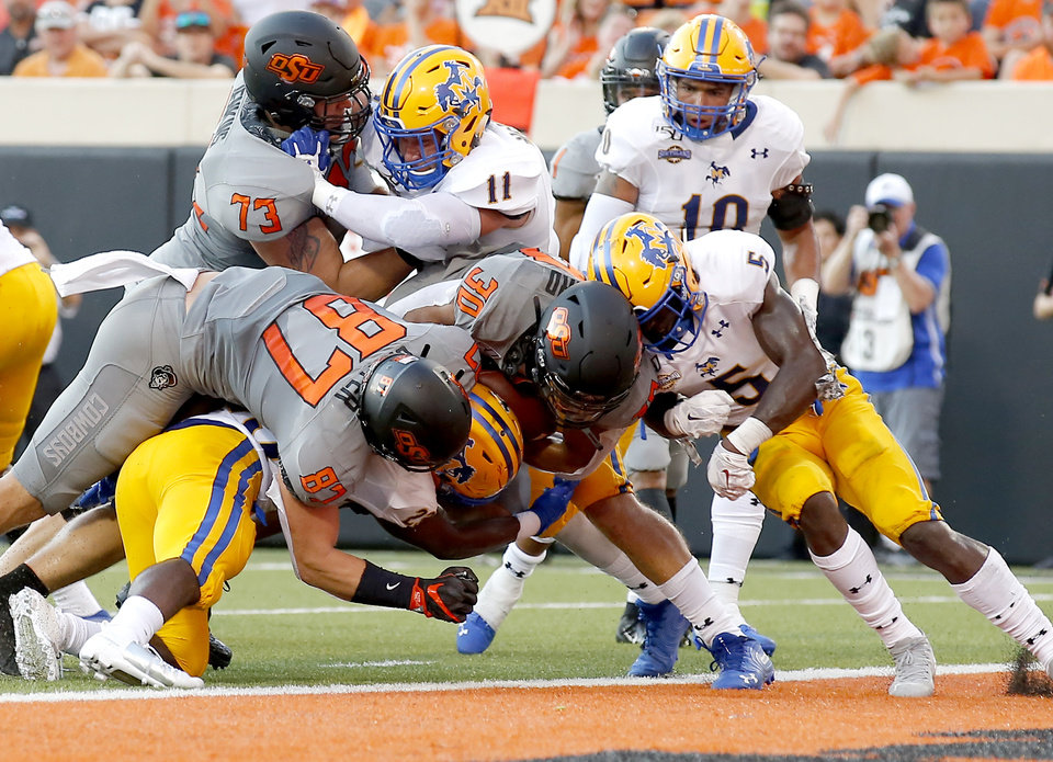 Photo - Oklahoma State's Chuba Hubbard (30) scores a touchdown in the second quarter during the college football game between the Oklahoma State Cowboys and the McNeese State Cowboys at Boone Pickens Stadium in Stillwater, Okla., Saturday, Sept. 7, 2019. [Sarah Phipps/The Oklahoman]