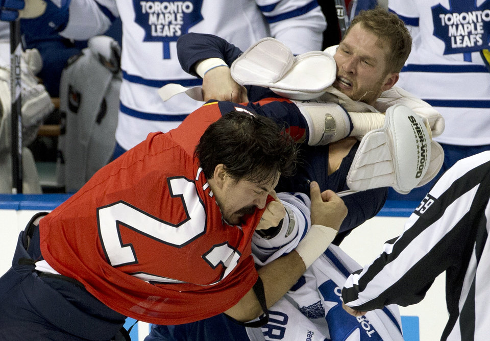 Photo - Florida Panthers' George Parros, left, and Toronto Maple Leafs' Colton Orr  fight during the first period of an NHL hockey game in Sunrise, Fla., Monday, Feb. 18, 2013.  (AP Photo/J Pat Carter)