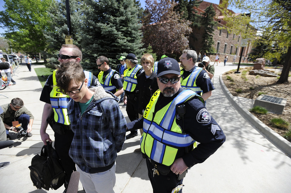 Photo -   University of Colorado senior Jonathan Edwards, front, and senior John Demopoulos, middle, are arrested by Boulder County Sheriff deputies for trespassing on Norlin Quad by going past the police tape on the University of Colorado campus in Boulder, Colo., on Friday, April 20, 2012. A block-long line of protesters marched onto the University of Colorado, testing the school's determination to push the annual April 20 marijuana celebration off campus. (AP Photo/The Daily Camera, Jeremy Papasso)