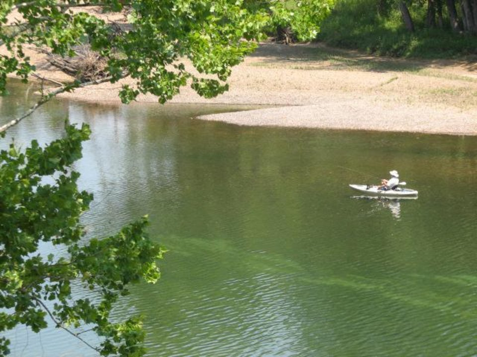 Photo - A trout angler makes his way downstream on the White River in a kayak. PHOTO BY ED GODFREY, THE OKLAHOMAN